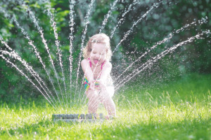 A girl is playing with sprinkler for small lawn