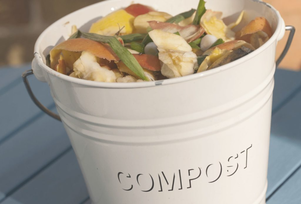a compost crock is filled up with kitchen food