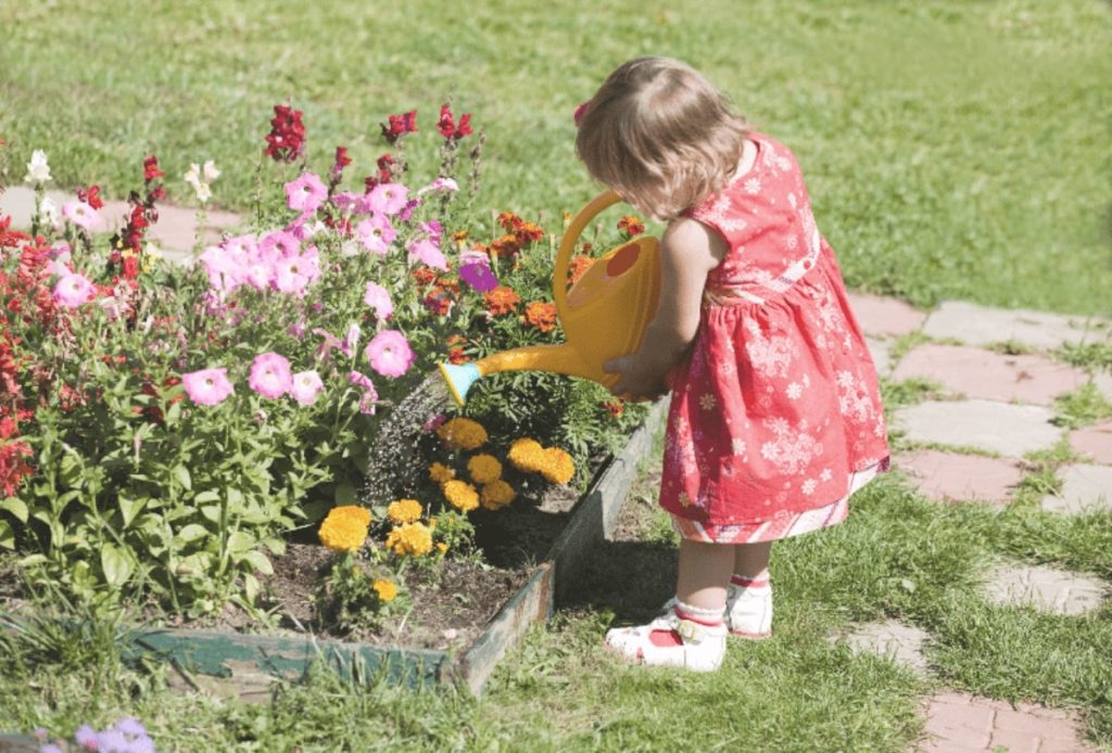 a lovely girl is working on low maintenance landscaping garden