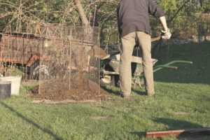 a man is using compost sifter